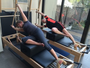 Pilates oefening op Reformer: side sit-up with stick
